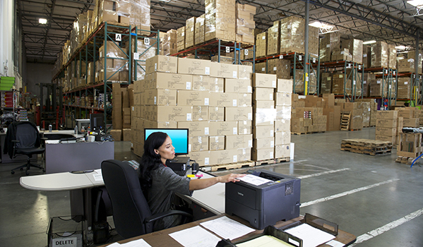 Person at shipper desk with printer preparing a shipment for FedEx